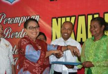 Menteri Pemberdayaan Perempuan dan Perlindungan Anak, Yohana Yembise, menyerahkan surat nikah pada salah satu pasangan nikah massal di aula Maranatha, KOta Sorong, Papua Barat, Kamis (21/12). (foto: ist/Penrem.)