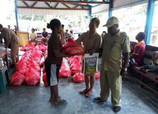 Sekretaris Perindagkop Teluk Wondama, Maria Sri Suliyanti SE, didampingi Kepala Perekda Dekky Torey, menyerahkan paket pasar murah seharga 70 ribu pada salah satu warga Kampung Maimari.