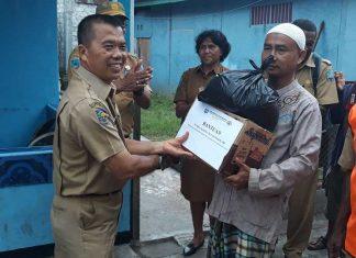 Ketua RT 04/RW 06 Kampung Maduraja, Kelurahan Wosi, Daryanto (kiri) saat menerima paket bantuan yang diserahkan Wanto, Asisten I Pemerintah Kabupaten Manokwari.